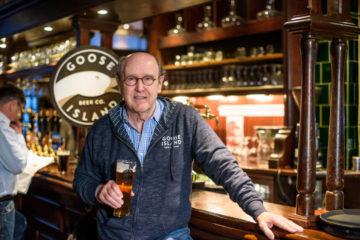 Äldre man som står med ett ölglas i pubmiljö.