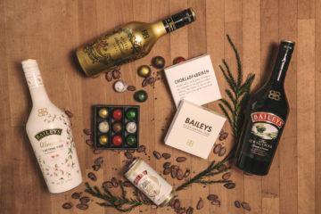 Ett läckert potpurri med touch av jul. Baileysflaskor, praliner och julströssel mot en träbakgrund.