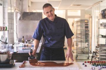 Martin Isaksson från Chokladfabriken jobbar med choklad och ser glad ut.