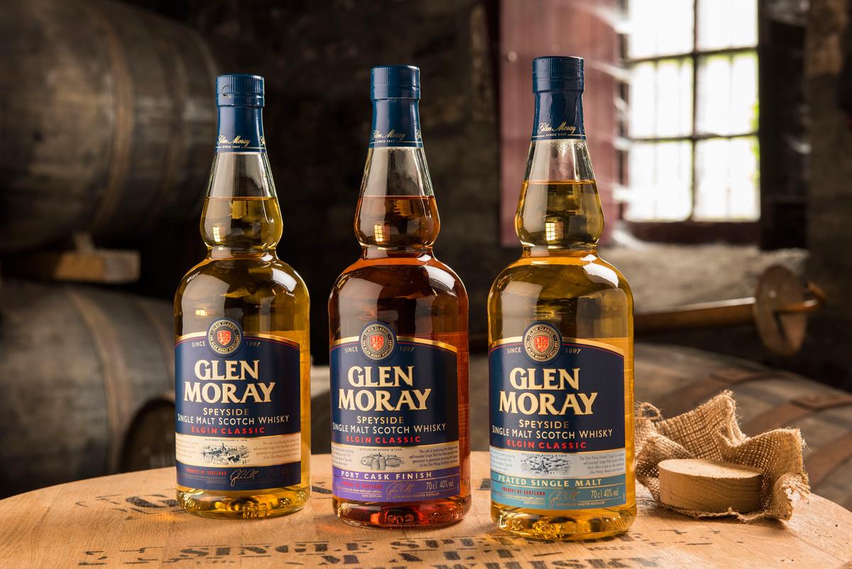 Tre Glen Moray-whiskies i lager. De tre flaskorna är vackert uppställda och ljussatta på ett whiskyfat