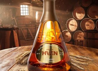 Hvenus rågwhisky från svenska Hven. Här framställd i sin karaktäristiska trekantiga flaska, belyst från ett fönster bakifrån i destilleriet.