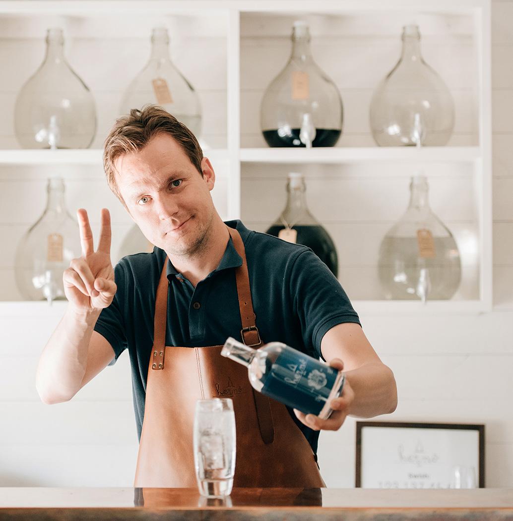 Hernö Gins grundare Jon Hillgren gör vinst-tecknet med fingrarna medan han häller upp en gin & tonic.