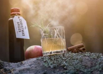 I motljus står Swedish Tonic Christmas spices tonic. på en vacker sten. Till höger i bild, en drink och glöggkryddan kanel, här i form av två kanelstänger.