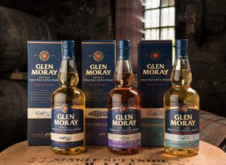 Tre Glen Moray-flaskor med kartong på ett whiskyfat i lagringshuset.