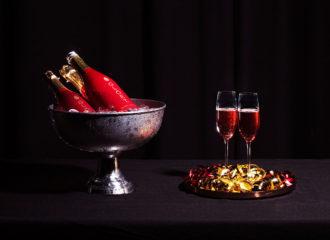 En champagnekylare och glas på en festligt utsmyckad bricka. Här serveras Glöet –en blandning av glögg och mousserande vin.