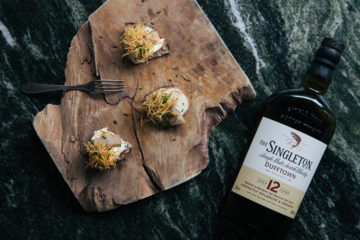 Några läckra matbitar på en bohemisk träskiva, en ensam gaffel och en flaska Singleton whisky fotograferat på Tjoget av Petter Bäckström