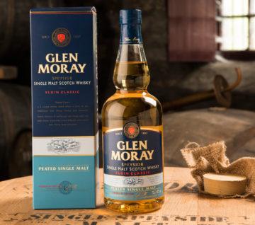 En flaska Glen Moray Peated med kartong ståendes på ett whiskyfat. Vackert, på något varmt vis.