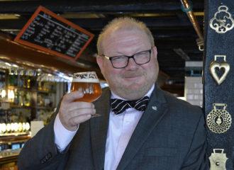 Rick Kempen står i baren med ett ölglas